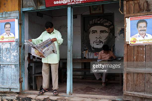 Indian men read newspapers in front of a cardboard cutout of Ernesto Che Guevara on October 18 2010 in Fort Cochin India Keralans are preparing to go...