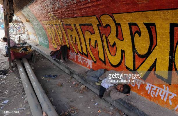 Indian men rest under a railway bridge on a hot summer day in Allahabad on April 14 2017 / AFP PHOTO / SANJAY KANOJIA