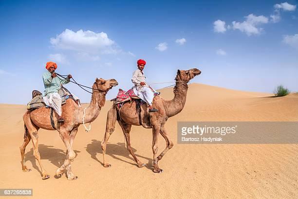 Indian men riding camels on sand dunes, Rajasthan, India