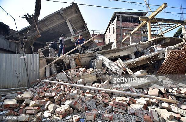Indian men search through the debris of a collapsed building following a 67 magnitude earthquake in Imphal on December 4 2015 At least eight people...