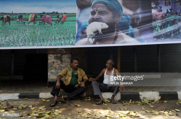Indian men sit beneath a poster of a farmer's protest during a statewide strike called by farmers in Chennai on April 25 2017 Tamil Nadu state...