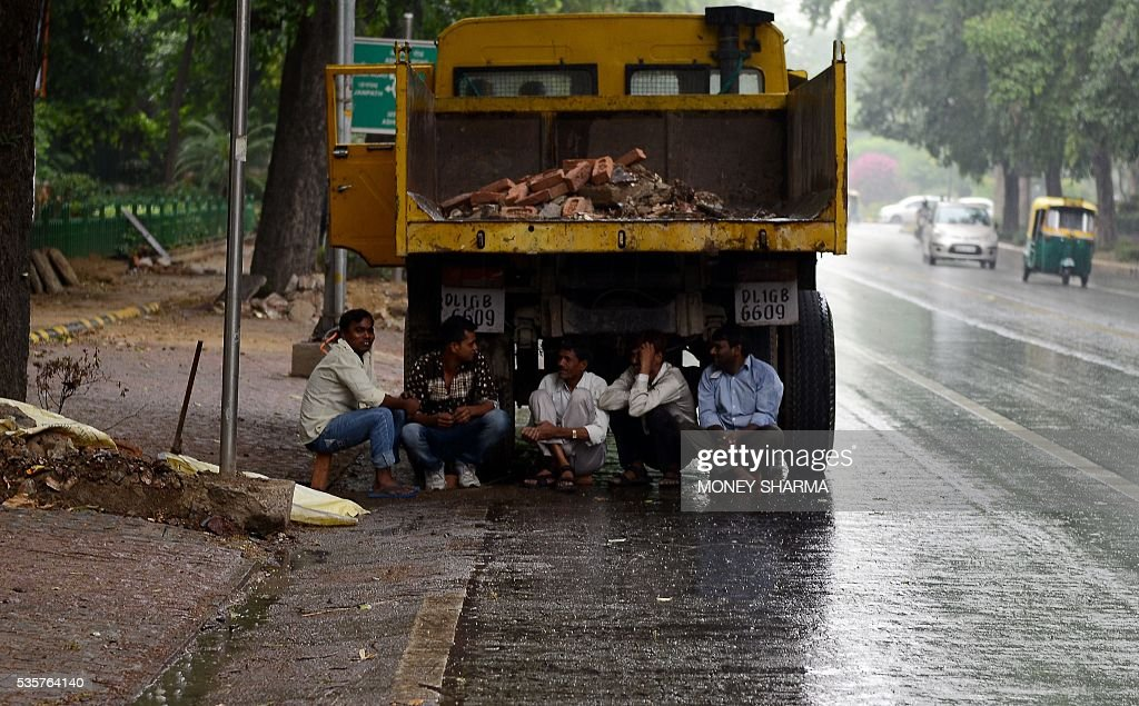 Indian men sit under a truck during a rain shower in New Delhi on May 30, 2016. / AFP / MONEY