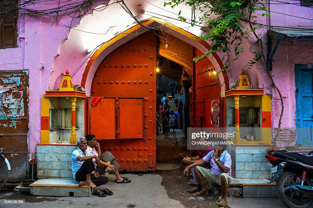 Indian men talk as they sit outside the main door of their house in the old quarters of New Delhi on May 31, 2016. / AFP / CHANDAN