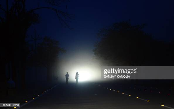 Indian men walk on a road during a dust storm in Allahabad on April 11 2015 AFP PHOTO/SANJAY KANOJIA