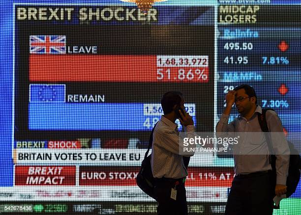 Indian men walk past a large screen showing news of Britain's vote to exit the European Union in Mumbai on June 24 2016 The pound collapsed to a...