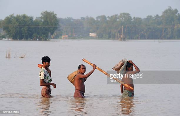 Indian men walk through a flooded area of Udaynarayanpur in Howrah district west of Kolkata on August 4 2015 Floods from days of torrential rain have...