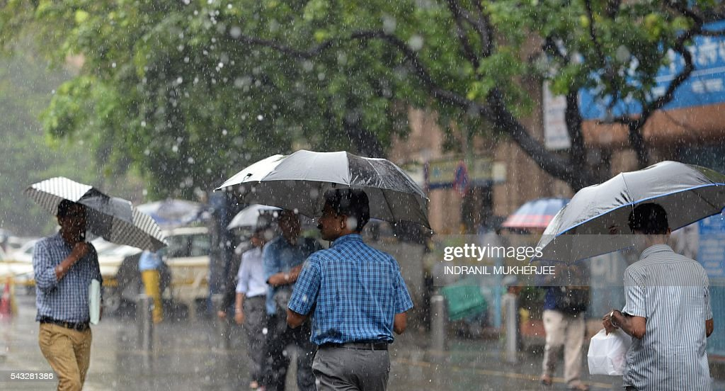 Indian men walk with umbrellas under heavy rain in Mumbai on June 27, 2016. Annual monsoon rains have progressed to most parts of western and central India, easing fears of millions of desperate farmers after two straight years of drought, the weather department said. / AFP / INDRANIL