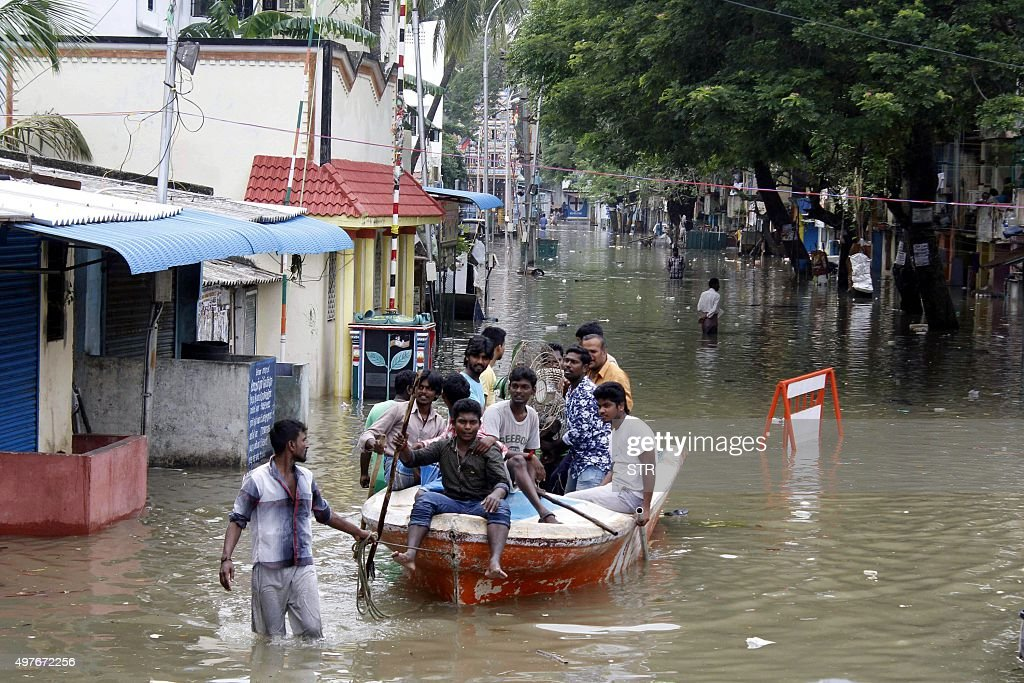 Indian men with a boat move people to safety on a flooded street after heavy rains in Chennai on November 18 2015 Large areas of the southern Indian...