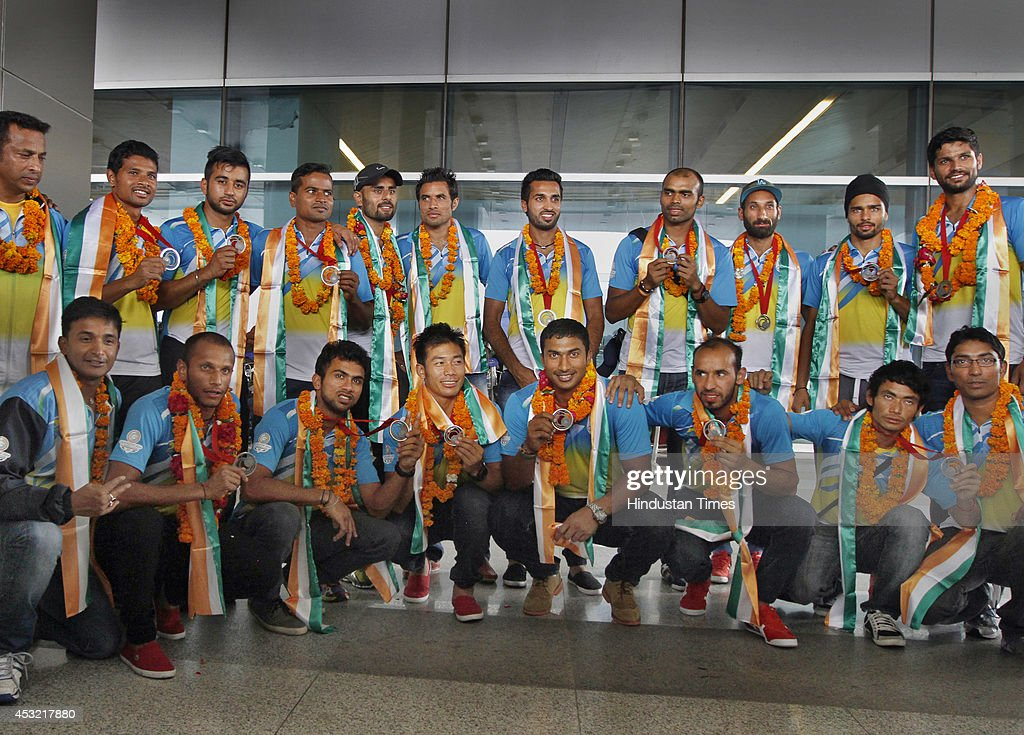 Indian men's hockey team players pose with their silver medals on arrival at the IGI Airport after participating in CWG 2014 held at Glasgow on August 5, 2014 in New Delhi, India.