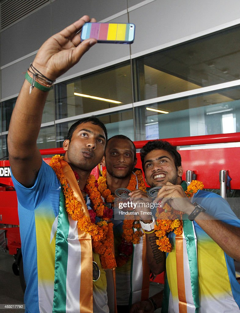 Indian men's hockey team players taking selfies on arrival at the IGI Airport after participating in CWG 2014 held at Glasgow on August 5, 2014 in New Delhi, India.