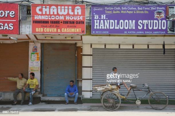 Indian merchants sit next to clothes market stores closed during a protest against the central government's move to levy a goods and services tax on...