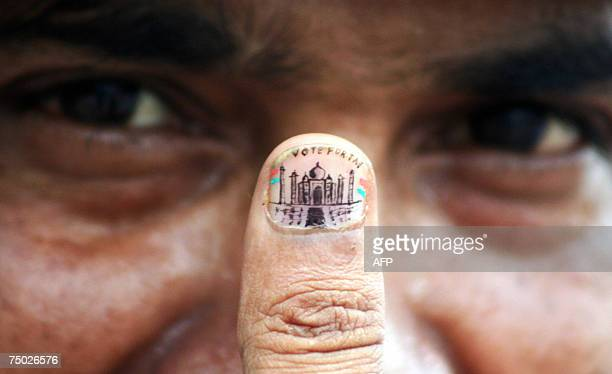 Indian microartist Ramesh Shah shows his thumb painted with a miniature image of the Taj Mahalas a gesture of support for the Tajs inclusion into the...