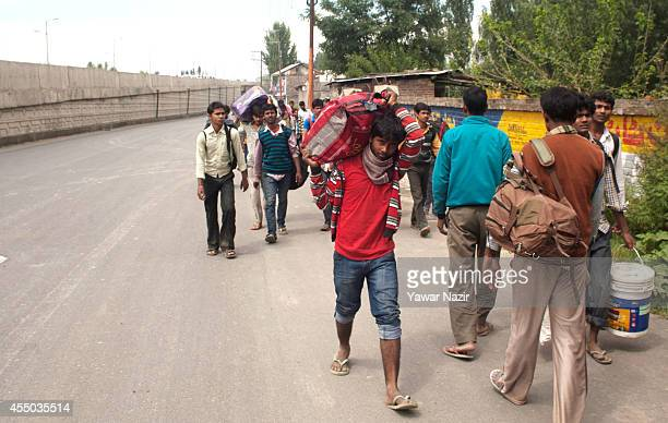 Indian migrants carry their luggage while they head towards airport to be evacuated by Indian Air Force planes on September 09 2014 in Srinagar the...