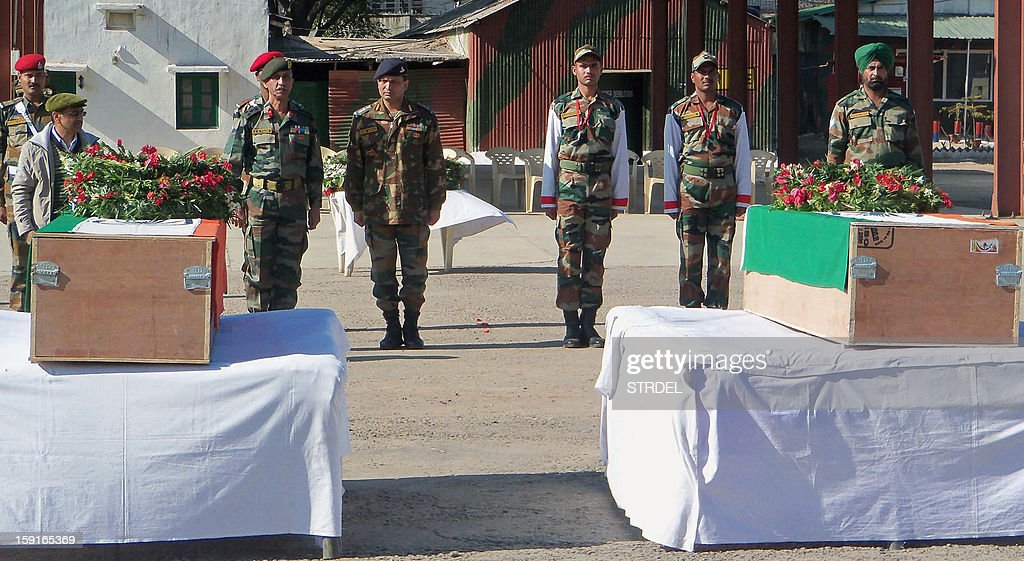 Indian military personnel pay their respects in front of the caskets bearing the bodies of Indian soldiers Lance Naik (Corporal) Sudhakar Singh and Lance Naik Hemraj, allegedly killed by Pakistani soldiers during a skirmish in the disputed Kashmir region, before their departure from Rajouri, some 150kms from Jammu, on January 9, 2013. India delivered a dressing-down to Islamabad's envoy to Delhi as it accused Pakistan's army of beheading one of two soldiers killed in Kashmir, but both sides warned against inflaming tensions.