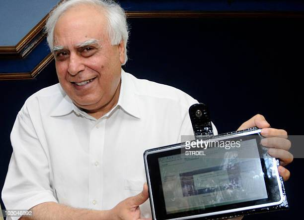Indian Minister for Human Resource Development Kapil Sibal unveils 'laptop' computer device in New Delhi on July 22 2010 India's ministry of human...