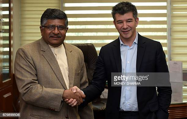 Indian Minister of Law and Justice and Ministry of Information Technology Ravi Shankar Prasad shakes hands with cofounder and CEO of Uber Travis...