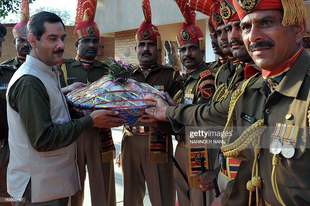 Indian Minister of State Sports and Youth Affairs, Jitendra Singh (L) gives a present to Indian Border Security Force (BSF) soldiers on his arrival at the international India-Pakistan Wagah Border on March 3, 2013. Singh visited to inspect the newly constructed Integrated Check Post (ICP) and also watch the beating retreat ceremony at Wagah border.