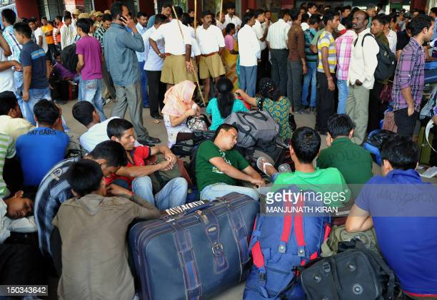 Indian minority northeastern residents wait at a train platform as they prepare to leave the city following rumours of communal violence against them...