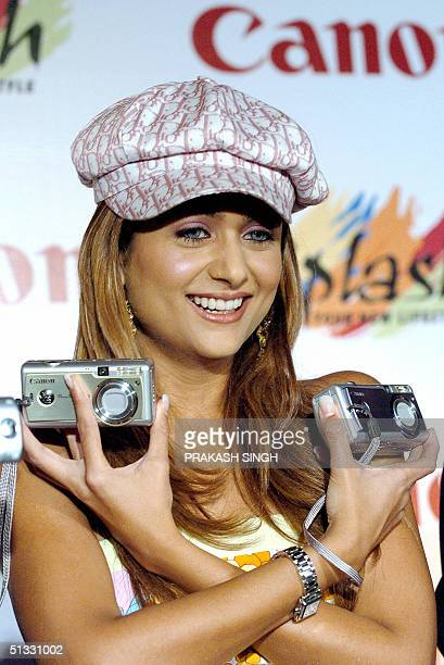 Indian model and Bollywood actress Amrita Arora poses with Canon digital cameras 'Power Shot A400' during a launch of Canon digital products for the...