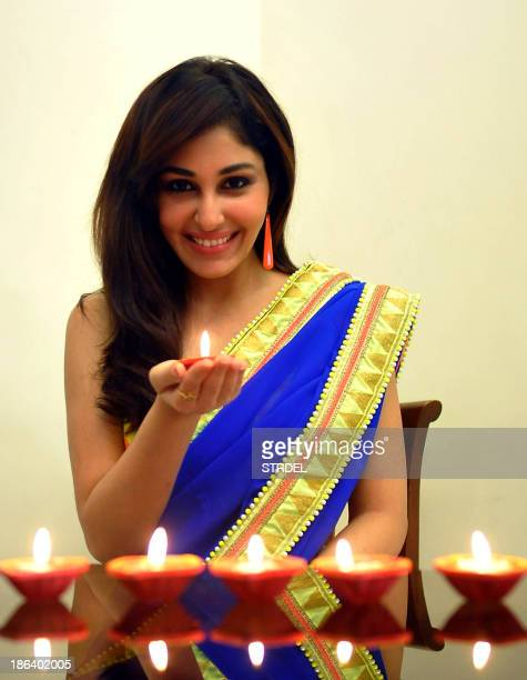 Indian model and Bollywood actress Pooja Chopra poses with candles during a celebration of the Hindu festival of Diwali in Mumbai late October 30...