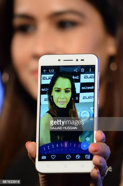 A Indian model displays the Asus ZenFone Live smartphone at a launch event in New Delhi on May 24 2017 Taiwanese mobile technology company Asus has...