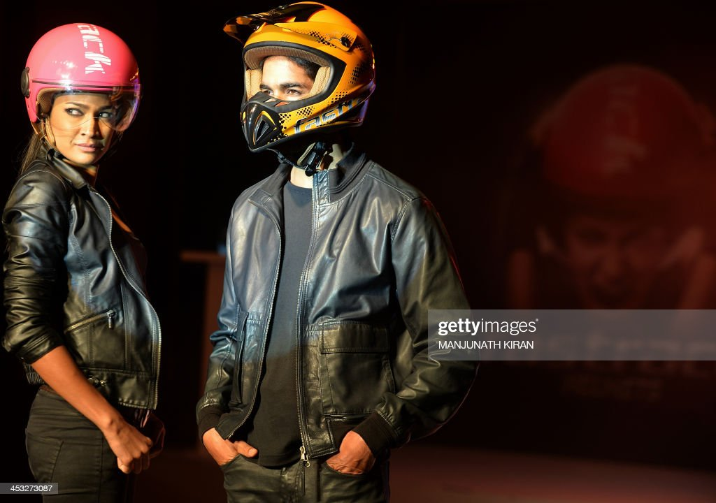 Indian models pose wearing Fastrack motorcycle helmets during the launch in Bangalore on December 3, 2013. Fastrack, a youth accessories brand of Titan Industries Limited, launched helmets manufactured in India in technical collaboration with Italy's AGV brand helmets. AFP PHOTO/Manjunath KIRAN