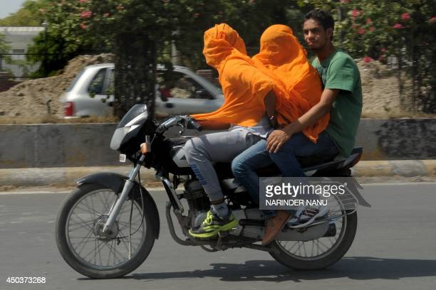 Indian motorcyclists cover their heads as they travel in the heat in Amritsar on June 10 2014 Amritsar and Ludhiana in Punjab and Hisar and Bhiwani...
