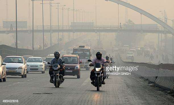 Indian motorists drive on a major road as smog covers the capital's skyline in New Delhi on October 20 2015 AFP PHOTO / PRAKASH SINGH