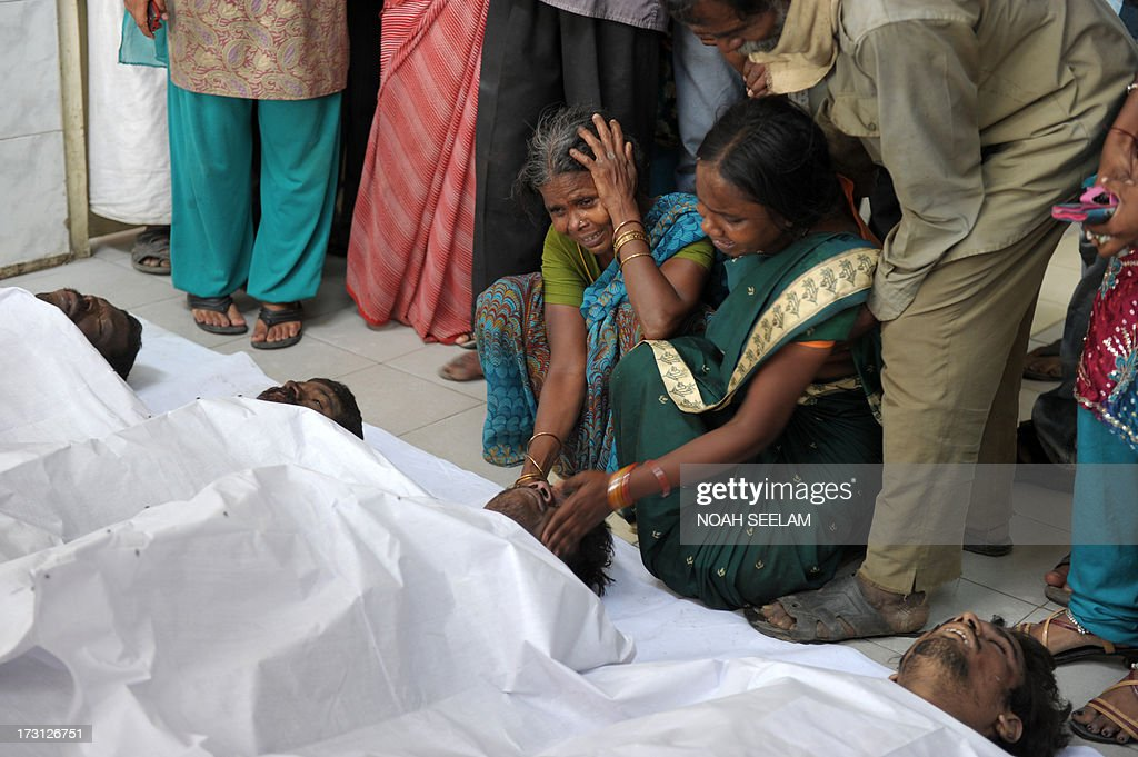 Indian mourners weep, as they kneel beside the bodies of those killed in a building collapse, in the mortuary at Gandhi Hospital in Secunderabad, the twin city of Hyderabad on July 8, 2013. A two-storey hotel collapsed in the southern Indian city of Secunderabad, killing at least 12 people and injuring 16 others, police said. Rescue workers were searching through tonnes of rubble for those still trapped after the incident in Andhra Pradesh state, local police official K. Satyanarayana told AFP. AFP PHOTO/Noah SEELAM