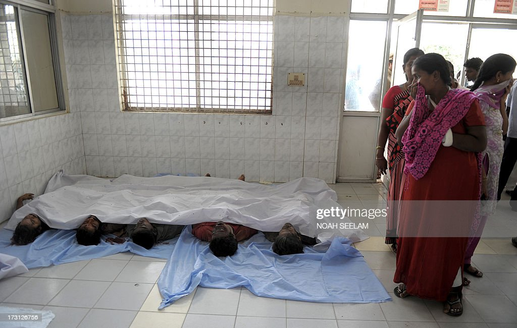 Indian mourners weep, as they stand beside the bodies of those killed in a building collapse, in the mortuary at Gandhi Hospital in Secunderabad, the twin city of Hyderabad on July 8, 2013. A two-storey hotel collapsed in the southern Indian city of Secunderabad, killing at least 12 people and injuring 16 others, police said. Rescue workers were searching through tonnes of rubble for those still trapped after the incident in Andhra Pradesh state, local police official K. Satyanarayana told AFP. AFP PHOTO/Noah SEELAM