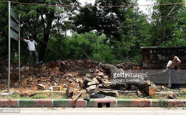 Indian municipal workers clear a tree that fell through a wall at the roadside after heavy rainfall in New Delhi on July 13 2015 India's captial has...