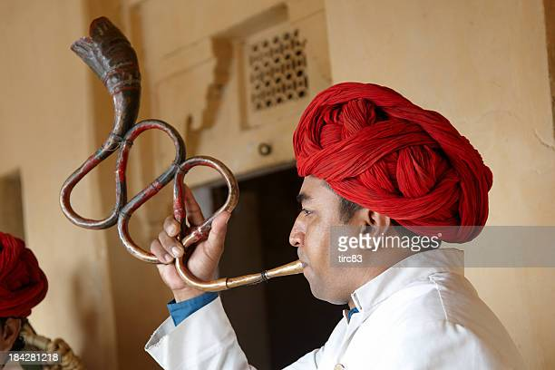 Indian musician playing curved trumpet type wind instrument