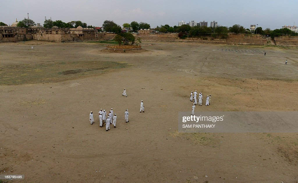 Indian Muslim boys play cricket on the dry bed of the Ahmad Sar Lake at Sarkhej Roza, the 15th century monument which houses the tomb of Saint Ahmed Khattu Baksh, spiritual counselor of Ahmedabad city's founder Ahmed Shah, southwest of Ahmedabad on March 16, 2013. Many districts of western Gujarat state, which received less monsoon rain than normal last year, are experiencing water scarcity. AFP PHOTO / Sam PANTHAKY