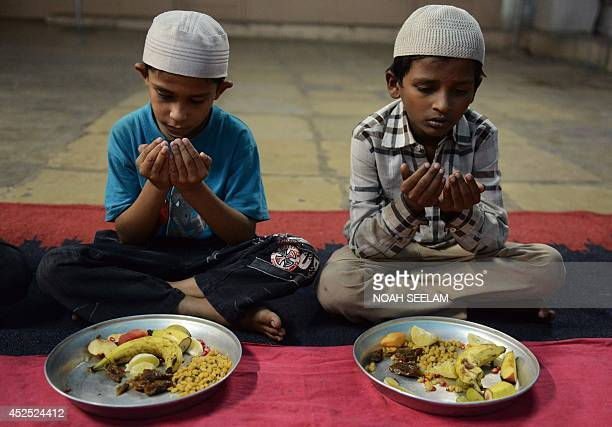 Indian Muslim children offer prayers prior to breaking their fast during of the holy fasting month of Ramadan at the AneesUlGhurba orphanage in...