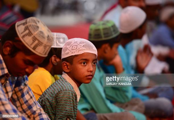 Indian Muslim children wait to break their fast outside a mosque on the first day of Ramadan in Allahabad on May 28 2017 Like millions of Muslim...