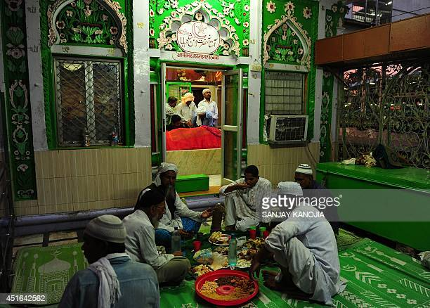 Indian Muslim devotees break their Ramadan fast outside the Shah Baba Mosque at Allahabad Junction railway station in Allahabad on July 3 2014 Like...