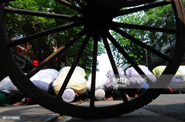 Indian Muslim devotees offer Friday prayers and a hand Rickshaw standing at the Kolkata Road side on the first Friday of Ramadan in Kolkata on June...