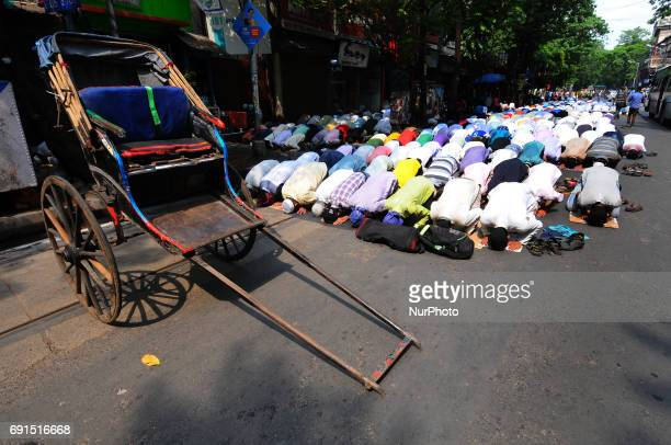 Indian Muslim devotees offer Friday prayers and a hand Rickshaw stand by at the Kolkata Road side on the first Friday of Ramadan in Kolkata on June...