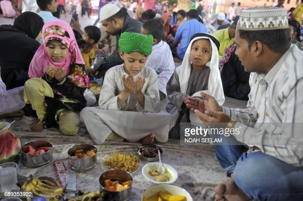 Indian Muslim devotees offer prayers before breaking their fast on the first day of the Islamic holy month of Ramadan at Mecca Masjid in Hyderabad on...