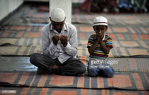 Indian Muslim devotees offers prayers before breaking the breaking of the Ramadan fast with Iftar at the MasjidESyednaOmar Farooq in Hyderabad on...