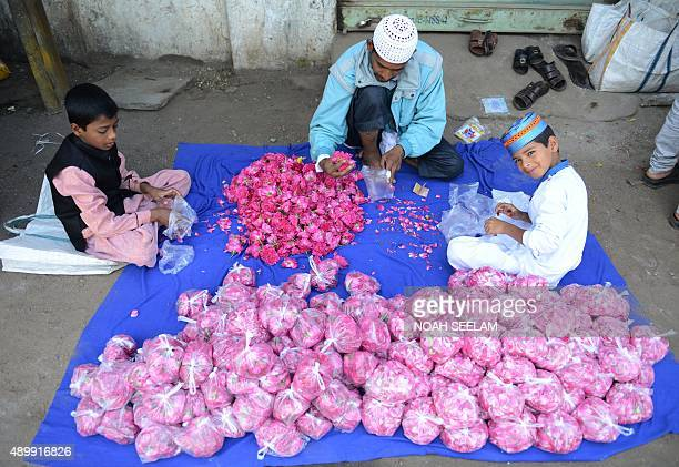 Indian Muslim devotees pack rose petals for devotees to leave as offerings on the graves of their relatives after Eid alAdha prayers in Hyderabad on...