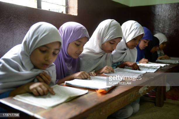 Indian Muslim girls recite the Holy Quran in their class room during the holy month of Ramadan at MadrasaturRashaad religious school in Hyderabad on...
