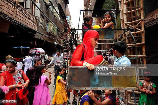 Indian Muslim kids taking joyrides during a fair on the occasion of Eidulfitr in the old quarter of city on July 29 2014 in New Delhi India The...