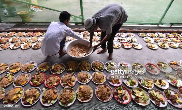 TOPSHOT Indian Muslim men arrange rows of food for Iftar the time for break the fast during the first day of the month of Ramadan in Guwahati on May...