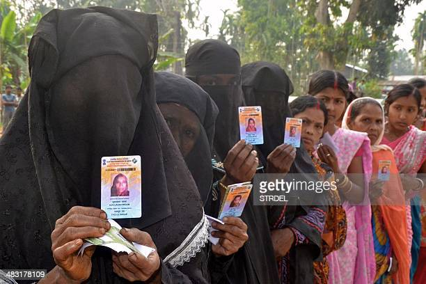 Indian Muslim voters pose with identification as they wait in line to vote outside a polling station in Koliabor in Assam state's Nagoan district...