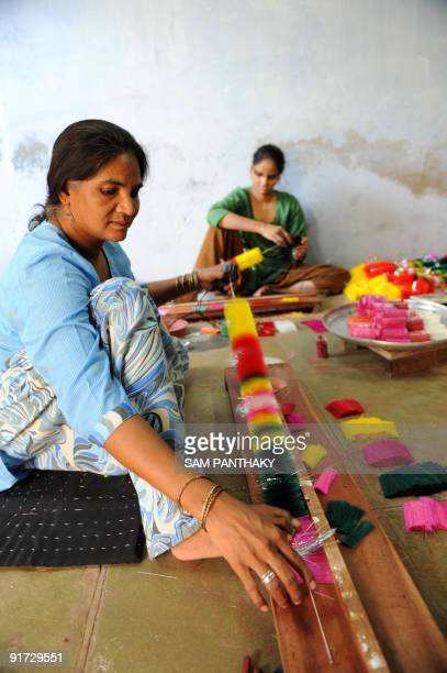 Indian Muslim women make silk garlands ahead of Diwali festivities in Ahmedabad on October 10 2009 Diwali which falls on October 17 this year marks...