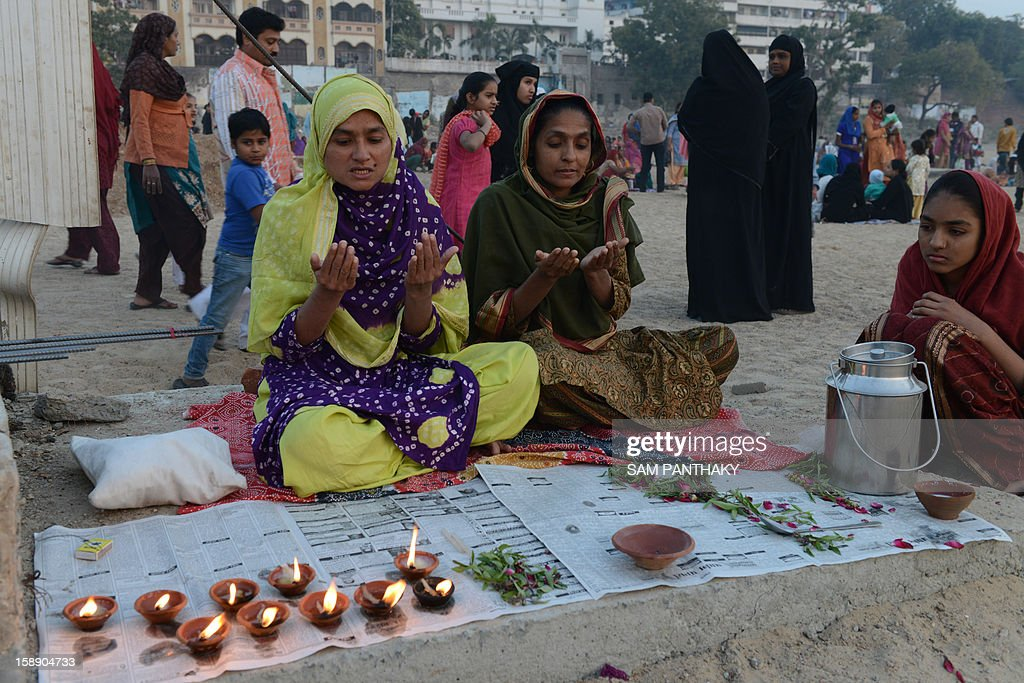 Indian Muslim women pray while observing 'Muhorram Ka Chalisa', which marks forty days after Moharram, on the banks of the Sabarmati river in Ahmedabad on January 3, 2013. Thousands of Muslims thronged the Sabarmati river bank near Khanpur Gate in Ahmedabad to mark the occasion. AFP PHOTO / Sam PANTHAKY