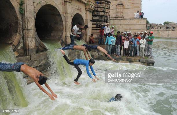 Indian Muslim youth dive as flood waters enter the tank of the 600 year old Sarkhej Roza architectural complex which has been dry for the last seven...