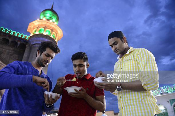 Indian Muslims break their fast on the first day of the Islamic holy month of Ramadan at Mecca Masjid in Hyderabad on June 19 2015 Like millions of...