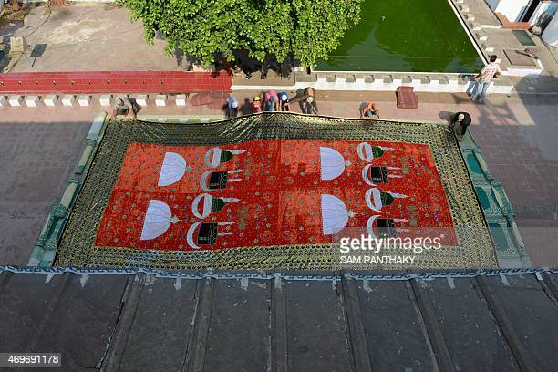 Indian Muslims display a ceremonial Chadar at the Siddi Saiyed Jaali Mosque in Ahmedabad on April 14 2015 According to the owner Gulam Mayuddin...